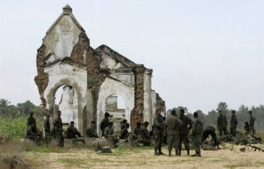Sri Lankan government soldiers rest in front of a ruined church.