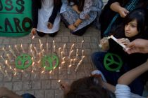 Pakistani youths light candle around peace signs during a ...