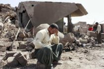 An Iraqi man sits in the ruins of a Kurdish village after a predawn ...