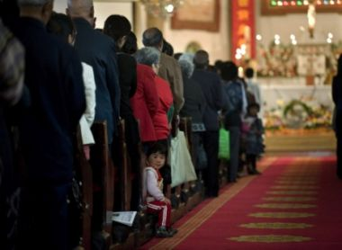 In this file photo, a child looks while Chinese Catholics participate ...