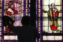 In this file photo, a worker cleans the window of a church in ...