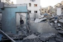 A Palestinian man sits in the rubble of a destroyed house after an ...