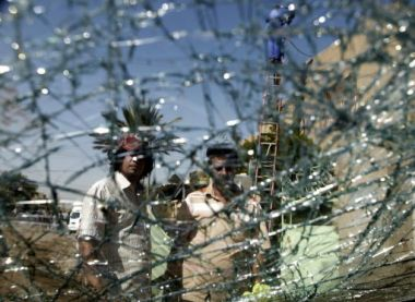 Iraqis are seen through a shattered windshield of a vehilce at the ...