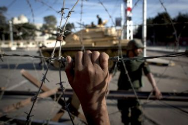 An Egyptian army tank is seen behind barbed wire securing the ...
