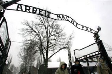Visitors walk through the entrance gate of the Auschwitz Nazi ...