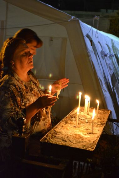 Christian woman prays at displacement camp
