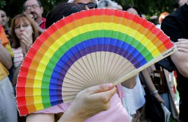 A gay rights activist refreshes with a fan during a pro-gay marriage ...