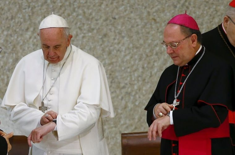 Pope Francis looks at watch