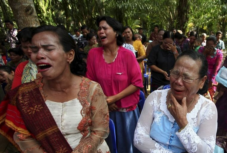 Indonesians cry during mass