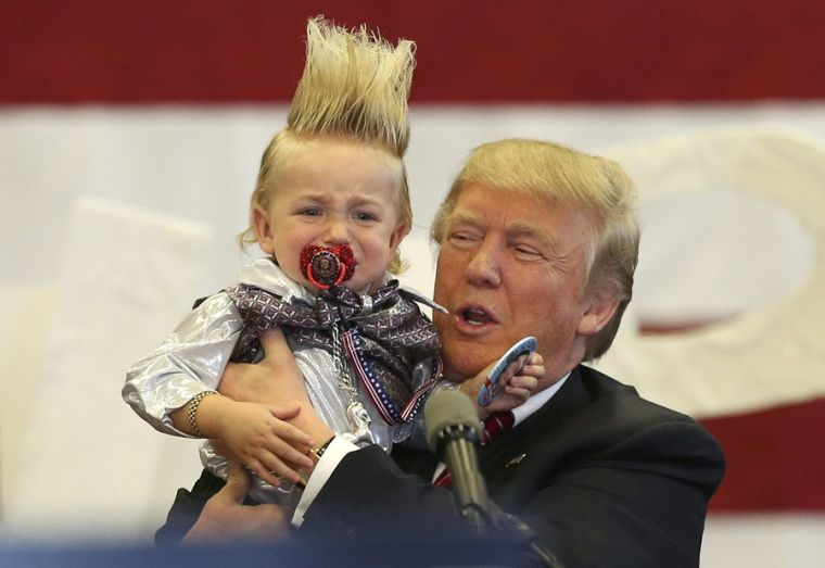 Donald Trump holds a crying boy with unusual hairstyle