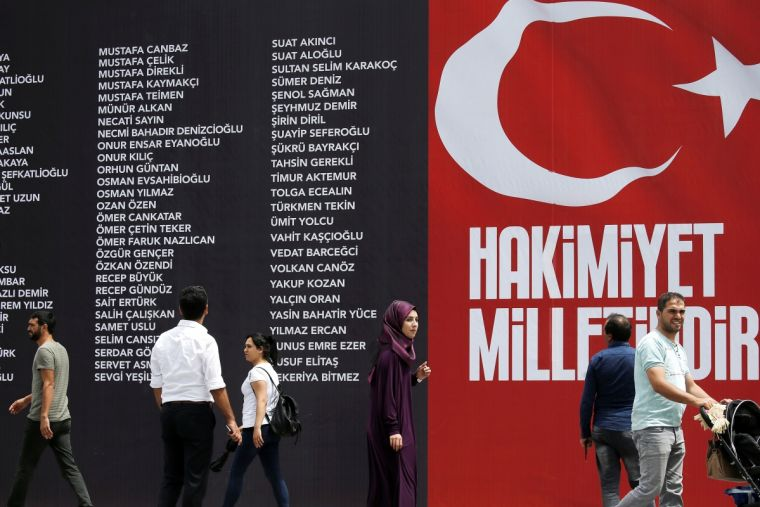People next to a banner read the names of civilians and police who were killed while resisting the coup attempt, on Taksim square in Istanbul, Turkey, earlier today. The slogan reads: 'Sovereignty belongs to the nation.'