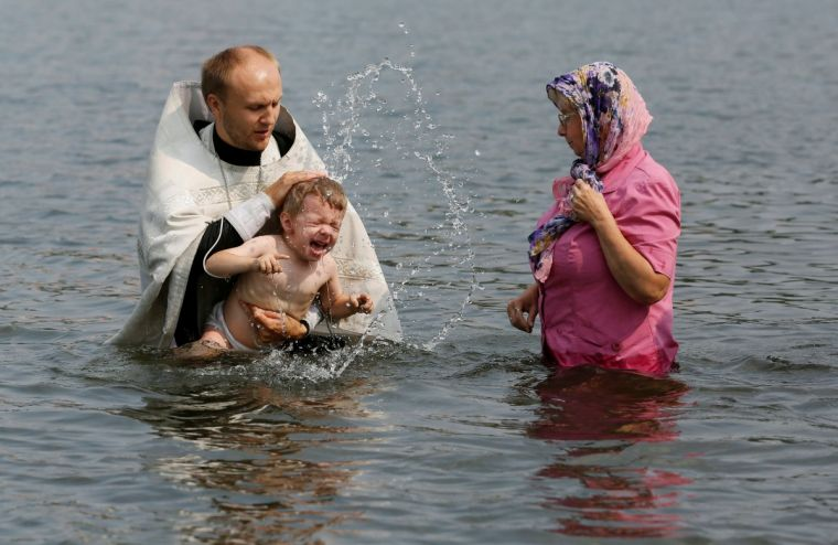 An orthodox priest baptises a child in the Yenisei river in Siberia during a ceremony in late July marking the Christianisation Russia