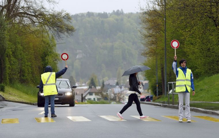 A Syrian migrant, on the right, works in a pilot project as a school patrol in the village of Boesingen near Freiburg, Switzerland in a photograph taken in April this year.