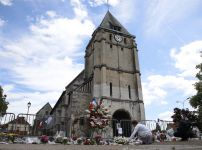 a-woman-places-flowers-to-pay-tribute-to-french-priest-father-jacques-hamel-outside-the-parish-church-at-saint-etienne-du-rouvray-near-rouen-france-where-he-was-murdered-in-july-by-islamist-extremists