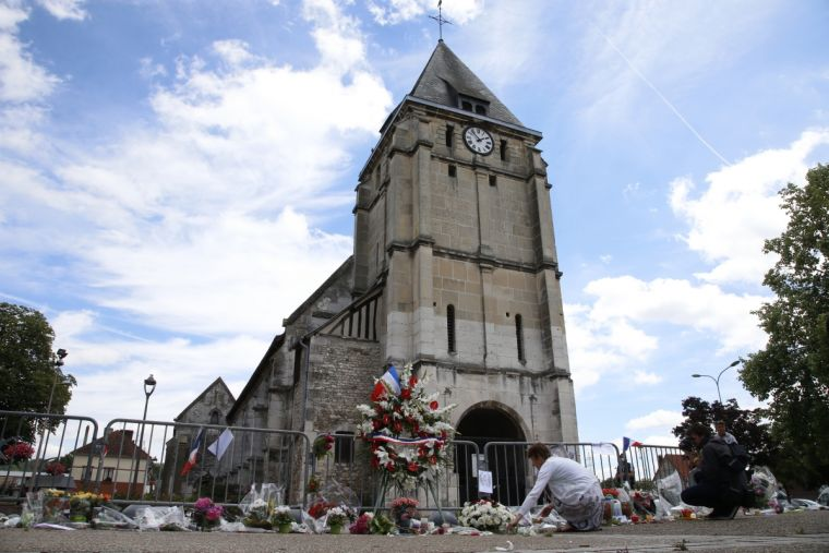 A woman places flowers to pay tribute to French priest Father Jacques Hamel outside the parish church at Saint-Etienne-du-Rouvray, near Rouen, France where he was murdered in July by Islamist extremists.