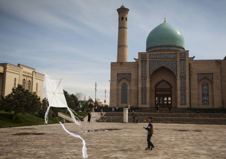 A boy plays with a kite at Khast Imam square in Tashkent, Uzbekistan