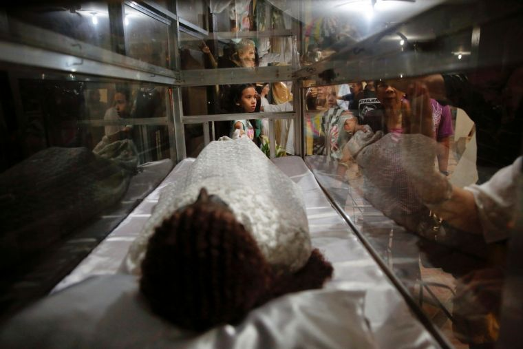 People gather around religious statues and objects after a service in a chapel at Camp Crame, the headquarters of Philippine National Police in Manila.