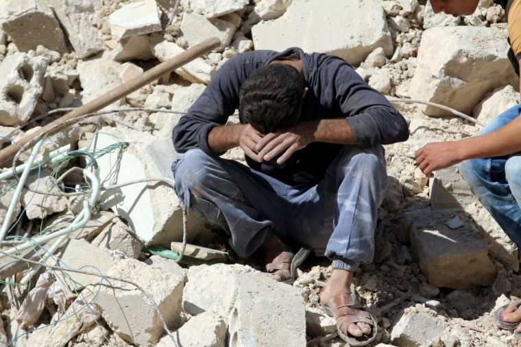 A man mourns relatives killed yesterday in the latest airstrike on the rebel-held al-Qaterji neighbourhood of Aleppo in Syria.