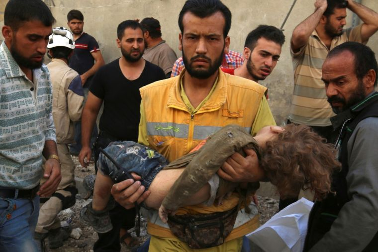 A man carries a child after an airstrike in Aleppo
