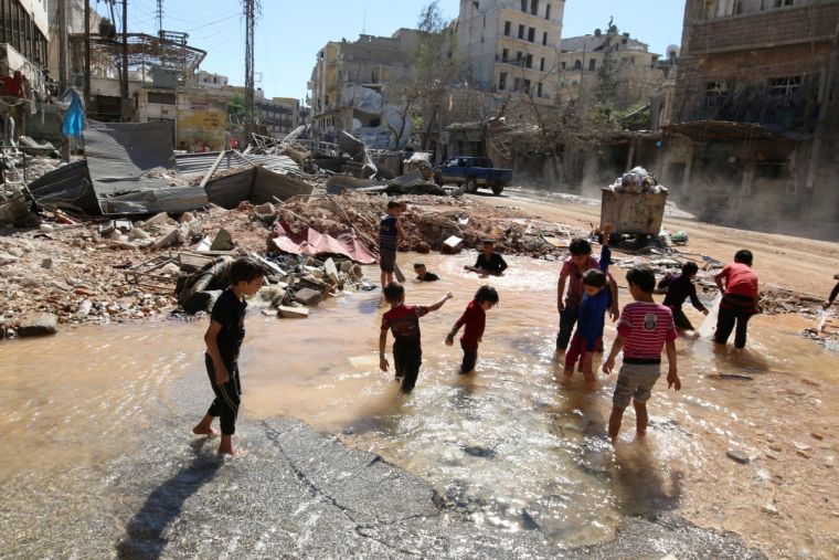 Children play in water amid devastation from an Aleppo airstrike on 30 September
