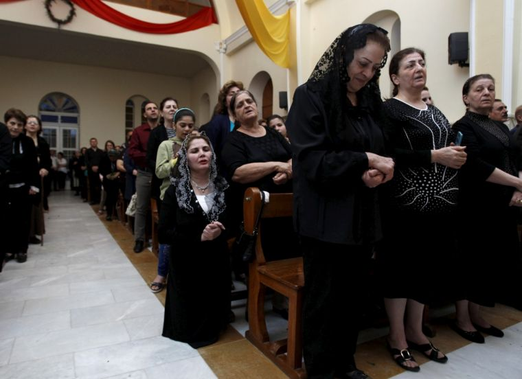Christian worshippers pray at a church in Baghdad
