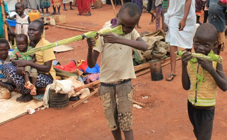 Martin Andrea, 10, and a friend play with toy guns made fromreeds at a displaced persons camp protected by UN peacekeepers in Wau, South Sudan,