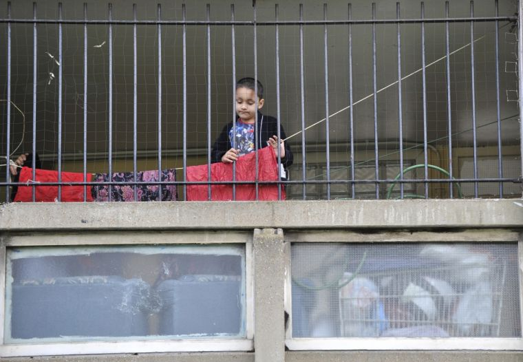 A child plays behind railings on the brutalist Robin Hood Gardens estate in Poplar, in East London.