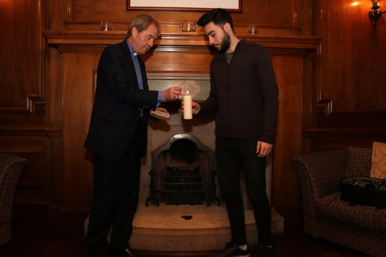 Rt Rev Dr Russell Barr and Gais Masri,19, who came to Scotland from Syria as a refugee, light a candle together