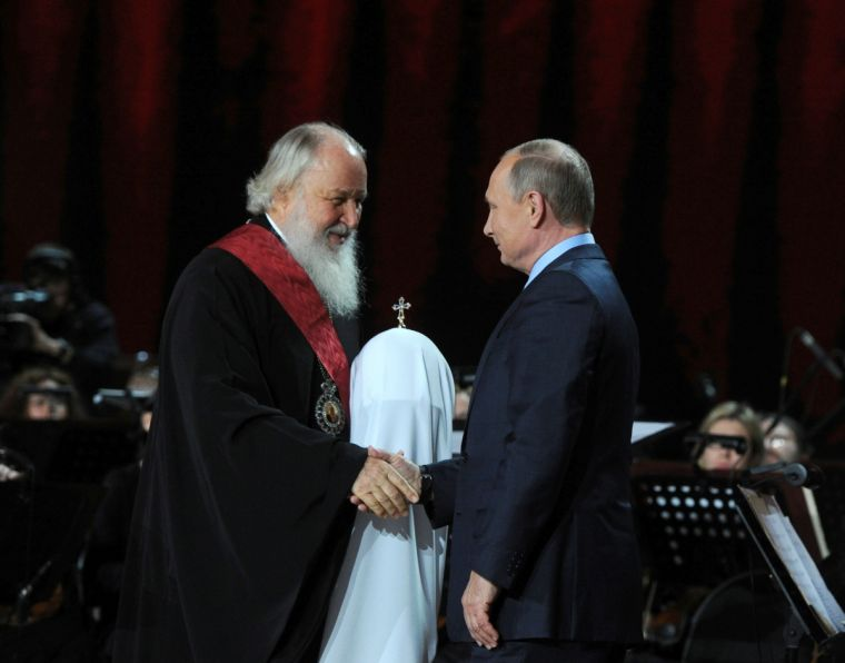 Russian President Vladimir Putin congratulates Patriarch Kirill of Moscow and All Russia on his birthday during a ceremony in Moscow