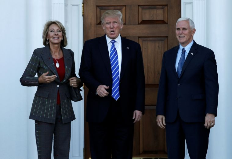 Donald Trump and Vice President-elect Mike Pence with Betsy DeVos at Trump National Golf Club in Bedminster, New Jersey.