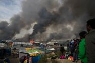 migrants-look-at-burning-makeshift-shelters-and-tents-in-the-calais-jungle-during-the-october-evacuation