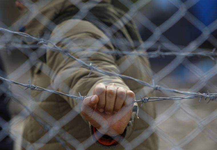 A migrant holds a barbed wire fence at the Macedonian-Greek border.