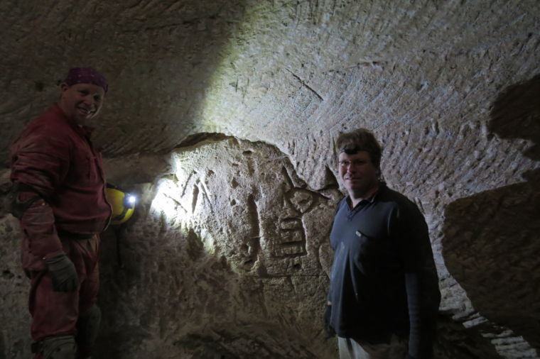 Hikers Ido Meroz and Mickey Barkal discover rare engravings of a Cross and a Menorah in an ancient water cistern in the Judean Shephelah
