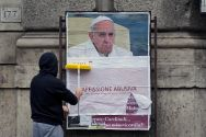 a-worker-covers-with-a-banner-reading-illegal-poster-a-poster-depicting-pope-francis-and-accusing-him-of-attacking-conservative-catholics