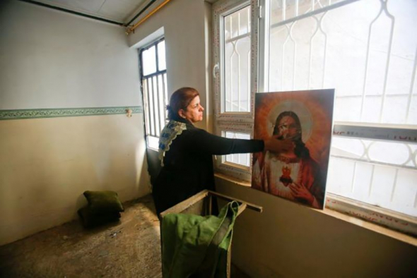 A Christian woman inspects a home in the town of Bartella east of Mosul, Iraq, after it was liberated from Islamic State militants, November 23, 2016.