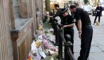 police-look-at-flowers-left-to-mark-victims-of-the-manchester-attack