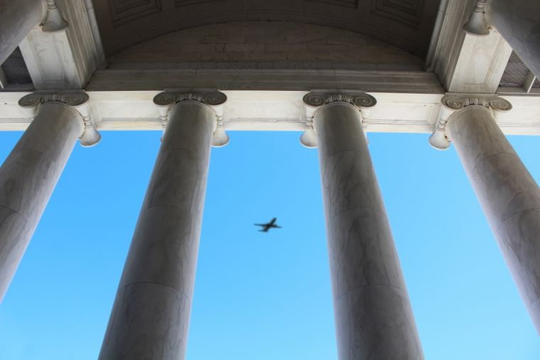 A plane viewed through columns of the Jefferson Memorial