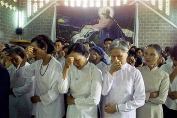 Vietnamese women make the sign of the cross during a mass at a church in Buon Ma Thuot, Vietnam.