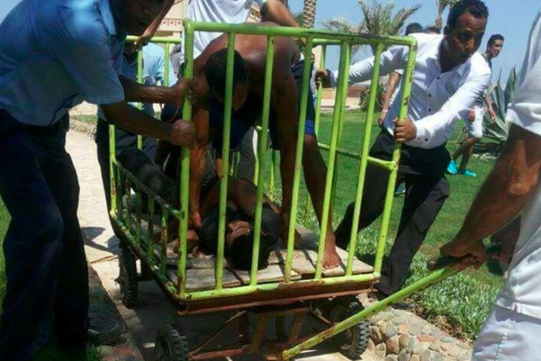 Workers and security detain the man who stabbed two German tourists to death and wounded four others during an attack of the Zahabia hotel resort in Hurghada, south of the capital Cairo, Egypt,