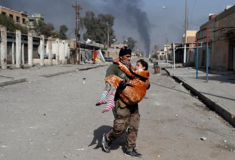 An Iraqi special forces soldier carries a woman injured during a battle between Iraqi forces and Islamic State