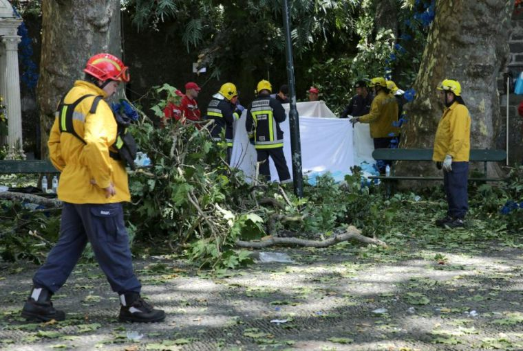 Firefighters cover victims of a tree that toppled into worshipping crowds during a religious festival in Funchal, Portugal,