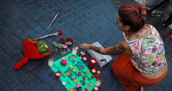 a-woman-places-a-candle-on-a-placard-reading-in-spanish-and-catalan-catalonia-place-of-peace-in-the-area-where-a-van-crashed-into-pedestrians-at-las-ramblas-street-in-barcelona-spain-august-18-2017