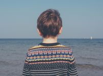 child-looks-out-at-ocean