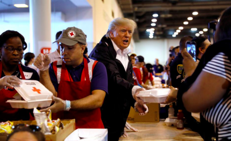U.S. President Donald Trump helps volunteers hand out meals during a visit with flood survivors of Hurricane Harvey
