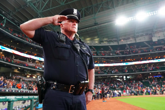 A Houston Police Officer salutes during a moment of silence at Minute Maid Field before the Houston Astros play the New York Mets in the first game after Tropical Storm Harvey in Houston, Texas