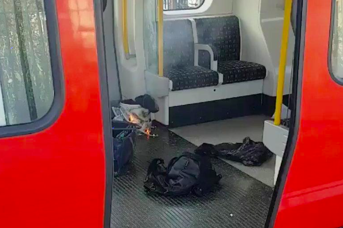 Personal belonglongs and a bucket with an item on fire inside it, are seen on the floor of an underground train carriage at Parsons Green station in West London, Britain September 15, 2017, in this image taken from social media