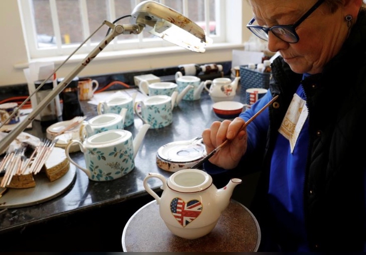 Sue Carter gilds a mug made to celebrate the Royal Wedding between Prince Harry and Meghan Markle