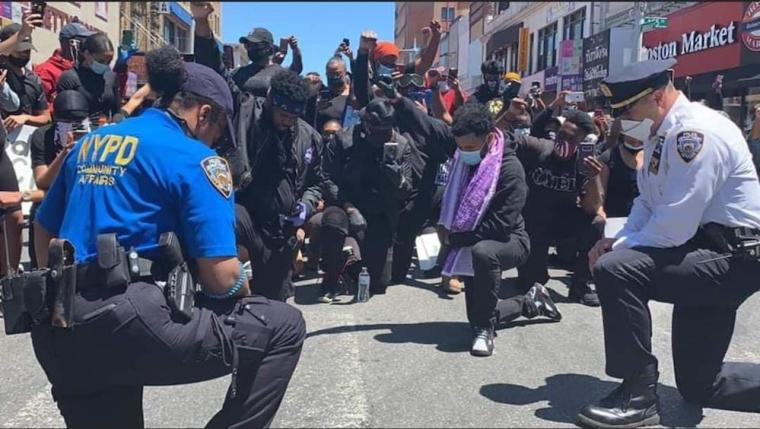Police officers kneel to pray with George Floyd protesters ...