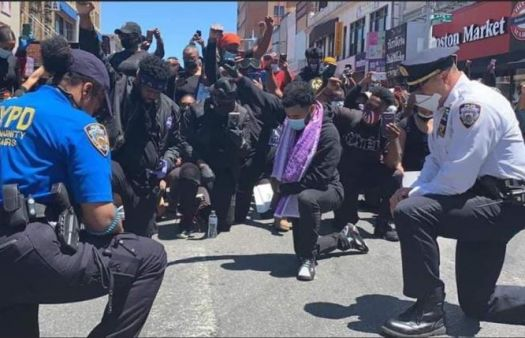 Police officers kneel to pray with George Floyd protesters