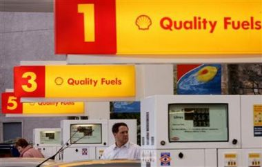People fill their cars with fuel at a Shell garage in Glasgow, ...